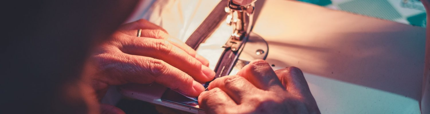 person playing sewing machine with white sewing machine